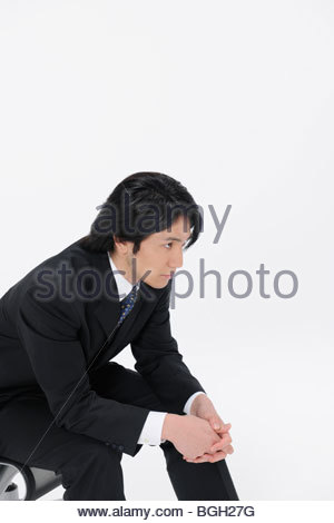 Young businessman sitting on chair white background - Stock Photo