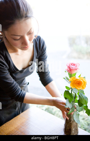 Young Woman Arranging Flower in Vase - Stock Photo
