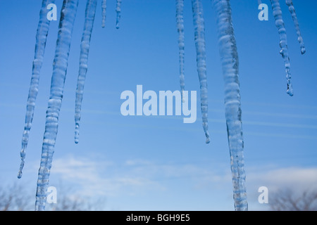 Close up abstract of Icicles hanging from roof of building against blue sky and snow. - Stock Photo