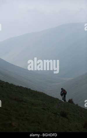 Mountain biker rides up a misty mountain trail in Howgill Fells, United Kingdom - Stock Photo