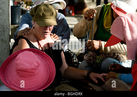 Woman tourist targetted by hawkers and masseurs, Kuta Beach, Bali, Indonesia - Stock Photo