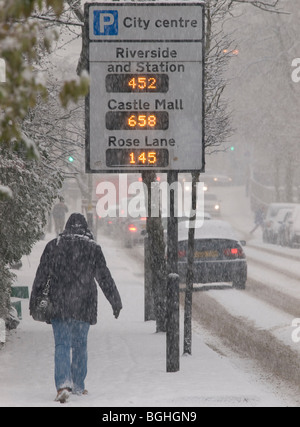 TRAFFIC IN THE SNOW ON RIVERSIDE ROAD NORWICH WITH ILLUMINATED SIGN INDICATING PARKING PACES AVAILABLE IN CITY CENTRE - Stock Photo
