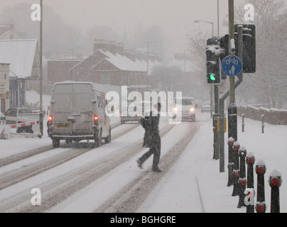 MAN CROSSING ROAD AT ZEBRA PEDESTRIAN WITH TRAFFIC IN THE SNOW ON RIVERSIDE ROAD NORWICH NORFOLK EAST ANGLIA ENGLAND - Stock Photo