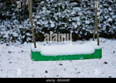 Green seat suspended by rope on which someone can sit and swing back and forth close-up winter covered with snow - Stock Photo