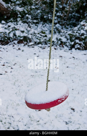seat suspended by rope on which someone can sit and swing back and forth close-up winter covered with snow - Stock Photo