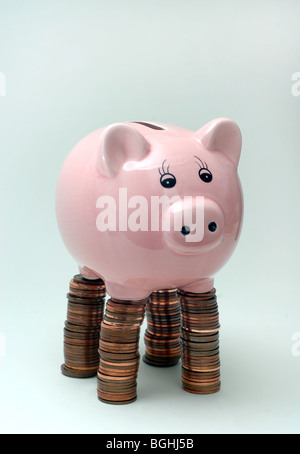 PIGGYBANK,PIGGYBANKS STANDING ON PILES OF BRITISH COINS RE THE ECONOMY SAVINGS INCOMES THE RECESSION BANKS CASH - Stock Photo