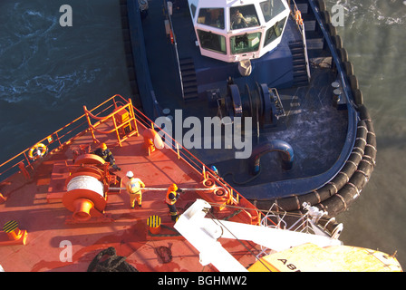 Crew members handle mooring lines while a tug waits below them at the stern of a ship. - Stock Photo