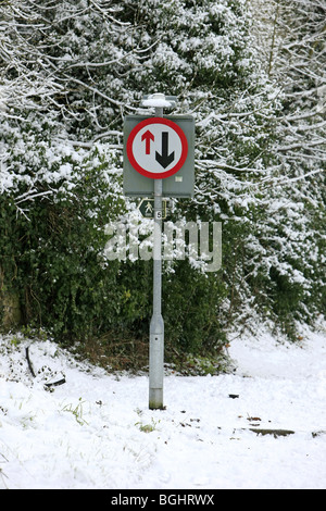 Give way to oncoming traffic sign on an impassable road during winter - Stock Photo