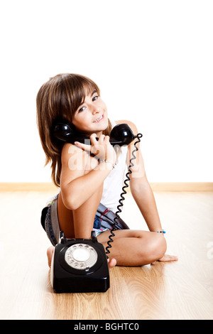 Little child making a phone call with a old vintage phone - Stock Photo