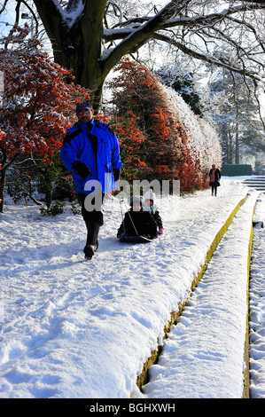 Children on sledge being pulled by Farther - Stock Photo
