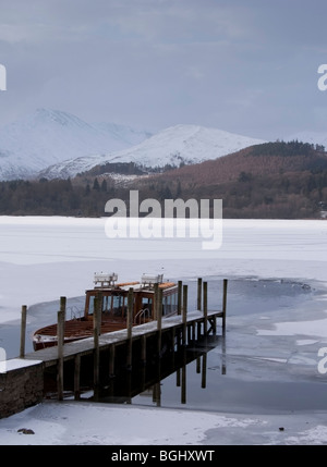 Boat tied to jetty on Derwent water in Keswick surrounded by ice. - Stock Photo