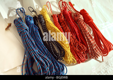 Coiled ropes, halyards, trimming and sheet lines lay on surface of folded sail. - Stock Photo