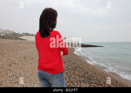 Back view of a woman wearing jeans and a red top, looking out to sea. - Stock Photo