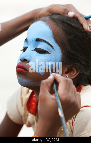 Indian girl having her face painted blue to be made up as an india deity. Andhra Pradesh, India - Stock Photo
