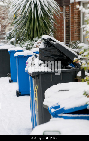 row of snow covered full recycle wheelie bins - Stock Photo