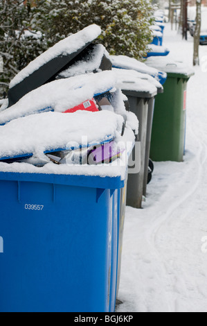 row of full snow covered wheelie recycle bins - Stock Photo