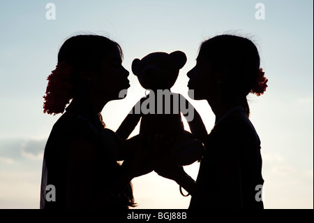 Indian girls kissing a teddy bear silhouette. India - Stock Photo