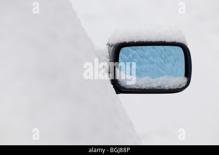 motor car wing mirror covered in snow - Stock Photo