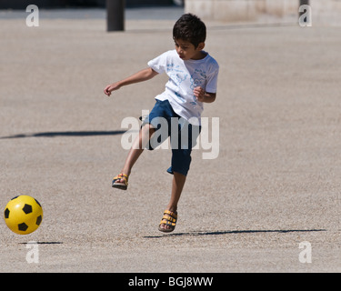 A single boy playing football on his own on tarmac in the playground - Stock Photo