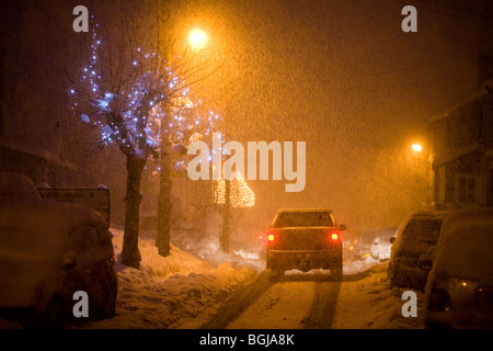 Car drives down a snow covered road at night. street lights and christmas lights light up the street - Stock Photo