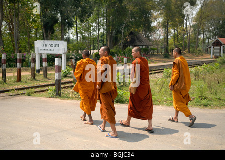 Four Buddhist monks walking along a road, Thamkrasae Bridge, Kanchanaburi district, Thailand - Stock Photo