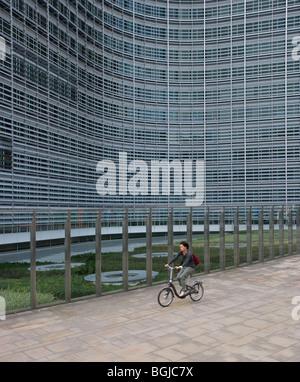 woman riding bicycle past berlaymont building - Stock Photo