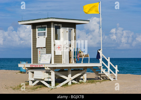 Palm Beach Shores , Florida , baywatch lifeguard hut with yellow flag flying against backdrop of blue sky & sea - Stock Photo