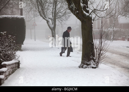 An elderly man struggles through the snow with shopping bags in Redditch, Worcestershire, UK - Stock Photo