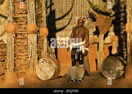 Zulu warrior in front of communal lodge, Shakaland, South Africa