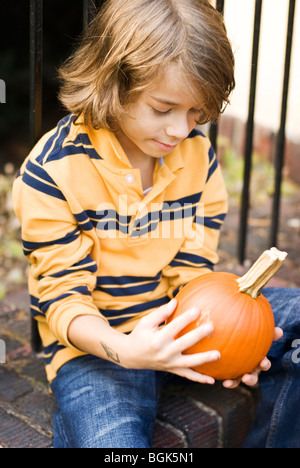 boy on steps with pumpkins - Stock Photo