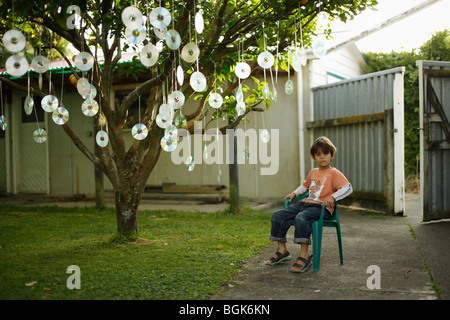 Boy sits beneath fruit tree with discs hanging from its branches - Stock Photo