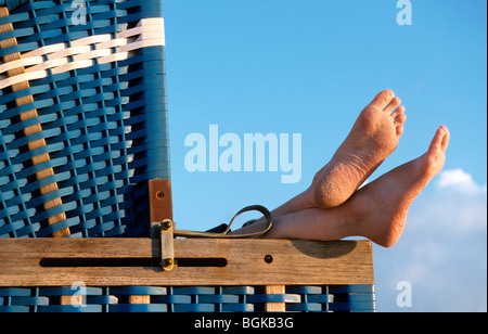 Bare feet sticking out from roofed wicker beach chair along the North Sea coast on the island Sylt, Germany - Stock Photo