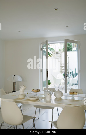 Dining area in renovated Grade II listed townhouse in Brighton with French windows and a spiral staircase. - Stock Photo