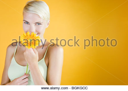 A Young Woman Holding An Orange Flower - Stock Photo