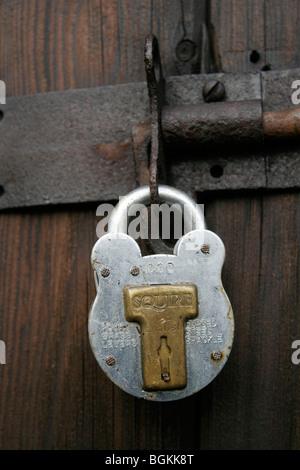 Squire Padlock On An Old Wooden Door - Stock Photo
