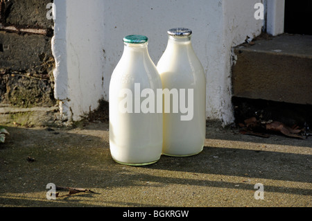 Two full milk bottles on doorstep, one green top and one silver North London England UK - Stock Photo