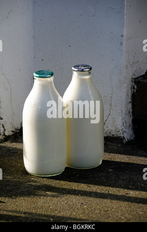 Two full milk bottles on doorstep, one green top and one silver London England UK - Stock Photo