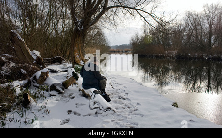 middle aged man sitting at gillingham beach beside frozen river waveney with snow on the ground in winter - Stock Photo