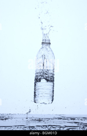 Bottle of water bouncing off surface and splashing - Stock Photo
