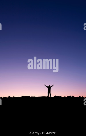 Silhouette of a man raising his hands into the sunrise after conquering a summit - Stock Photo