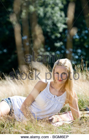 A young woman lying on the grass, looking at camera - Stock Photo