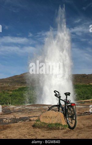 Bicycle in front of erupting Strokkur / churn, fountain geyser in the geothermal area beside the Hvítá River in - Stock Photo