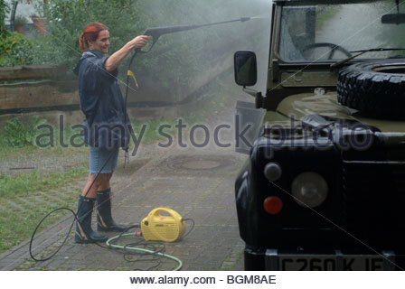 Person thinking alone young woman washing car land rover with water jet sprayer spray spraying - Stock Photo