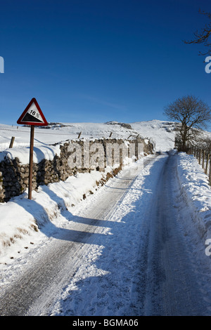 An icy, snow covered road with a 16% gradient warning sign - Stock Photo