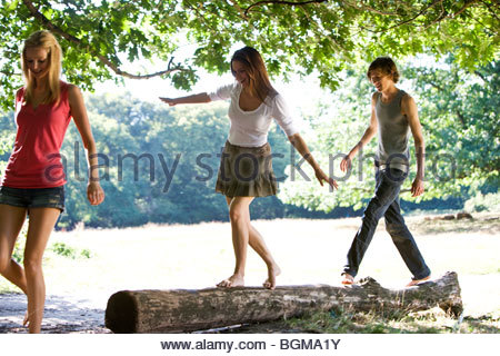 Three young people in a park, two balancing on a log - Stock Photo