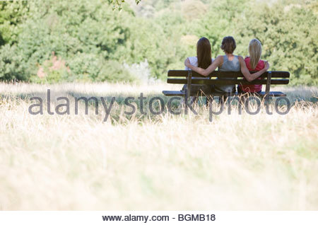 Three young people sitting on a bench in a park - Stock Photo
