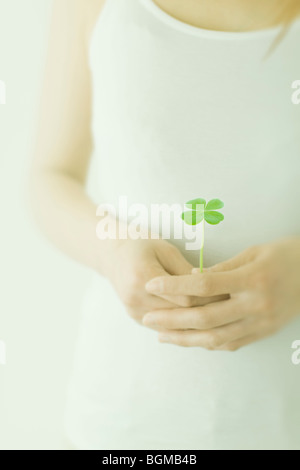 Women's hand holding a four leaf clover - Stock Photo