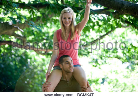 A young man carrying his girlfriend on shoulders in the woods - Stock Photo