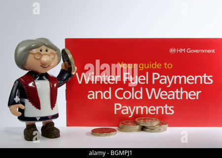 Model of old lady holding money next to a government leaflet for winter fuel and cold weather payments - Stock Photo