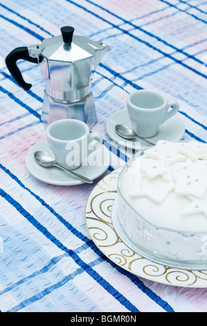 Christmas cake, espresso maker with espresso cups and saucers on a seersucker tablecloth - Stock Photo